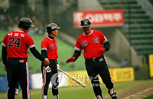 In this file photo taken April 10, 1992, Jang Chae-geun (R) of the Haitai Tigers celebrates a home run against the OB Bears with teammates at Jamsil Stadium in Seoul. (Yonhap)