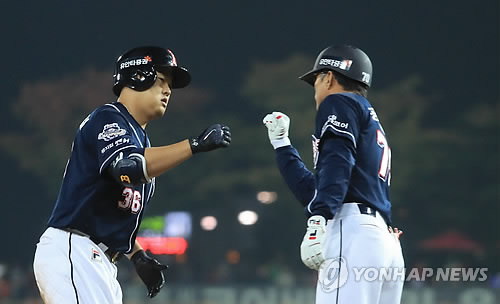 Oh Jae-il of the Doosan Bears (L) celebrates his solo home run against the Kia Tigers with his third base coach Kong Pill-sung in the top of the fifth inning in Game 1 of the Korean Series at Gwangju-Kia Champions Field in Gwangju on Oct. 25, 2017. (Yonhap)