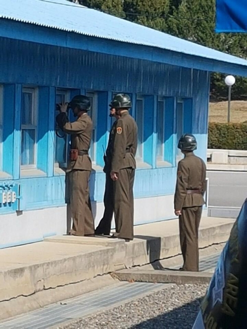 North Korean guards look through the window of the U.N. Command Military Armistice Commission's (UNCMAC) conference building as U.S. Secretary of Defense tours it on Oct. 27, 2017. (Yonhap)