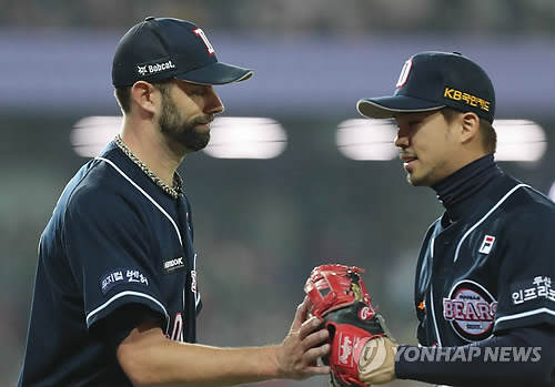 Dustin Nippert of the Doosan Bears (L) high-fives second baseman Oh Jae-won after completing the bottom of the second inning against the Kia Tigers in Game 1 of the Korean Series at Gwangju-Kia Champions Field in Gwangju on Oct. 25, 2017. (Yonhap)