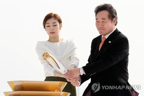 Former Olympic figure skating gold medalist Kim Yu-na (L) and South Korean Prime Minister Lee Nak-yon light the mini Olympic cauldron during the ceremony marking the arrival of the Olympic flame for the 2018 PyeongChang Winter Games at Incheon International Airport on Nov. 1, 2017. (Yonhap)