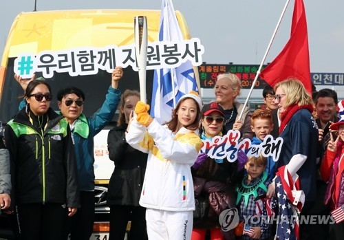 South Korean figure skater You Young (C) poses with the torch for the 2018 PyeongChang Winter Olympics on Incheon Bridge in Incheon on Nov. 1, 2017. (Yonhap)