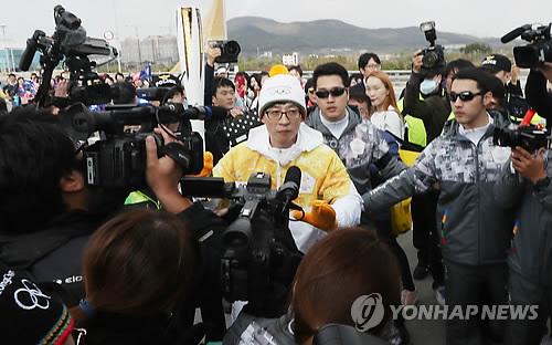 South Korean TV personality Yoo Jae-suk (C) bears the torch for the 2018 PyeongChang Winter Olympics on Incheon Bridge in Incheon on Nov. 1, 2017. (Yonhap)