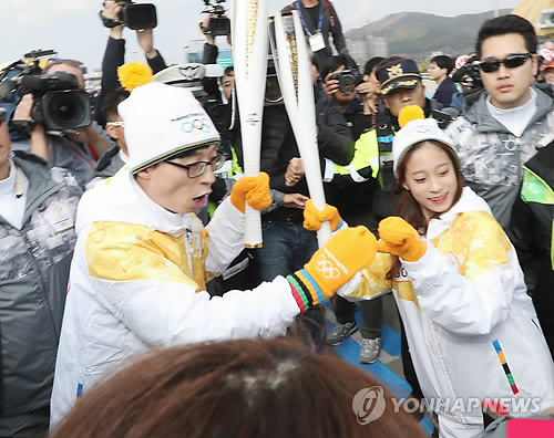 South Korean figure skater You Young (R) relays the Olympic flame for the 2018 PyeongChang Winter Games to TV personality Yoo Jae-suk on Incheon Bridge in Incheon on Nov. 1, 2017. (Yonhap)