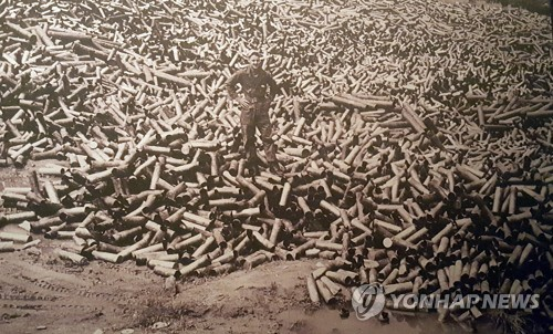 This file photo, exhibited at the 2nd Infantry Division's museum, shows an American soldier standing on a pile of empty shells during the Korean War. (Yonhap)