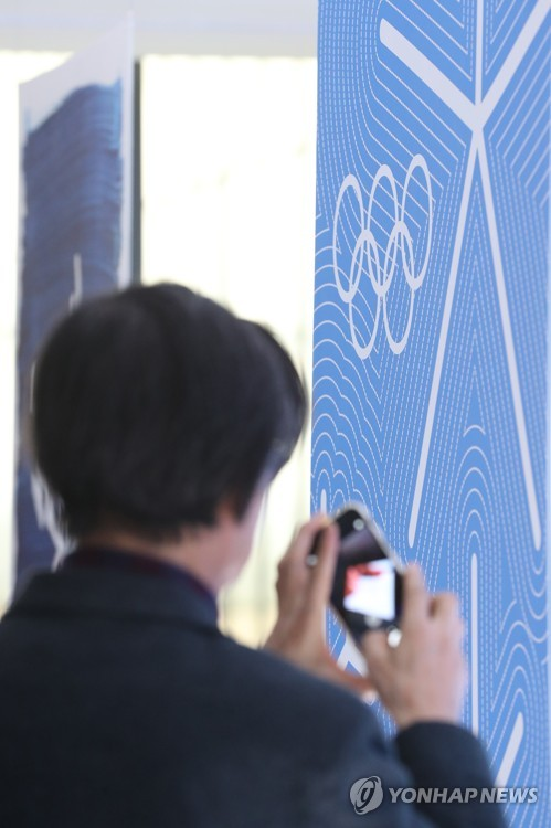 A visitor takes a photo of one of the winning posters about the PyeongChang Winter Olympics at the Seoul branch of the National Museum of Modern and Contemporary Art on Nov. 1, 2017. (Yonhap)