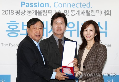 South Korean acting couple of Yoo Dong-kun (C) and his wife Jeon In-hwa (R) receive a plaque from Lee Hee-beom, head of the 2018 PyeongChang Winter Olympics organizing committee, after being named the event's honorary ambassadors in a ceremony in Seoul on Nov. 6, 2017. (Yonhap)
