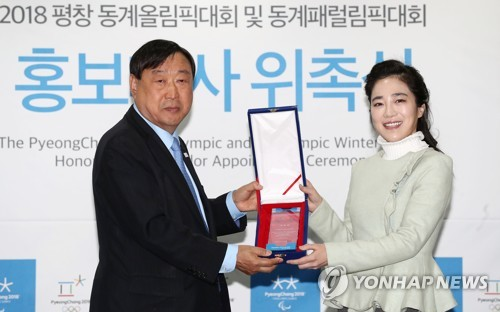 South Korean violinist Park Ji-hae (R) takes a plaque from Lee Hee-beom, head of the 2018 PyeongChang Winter Olympics organizing committee, after being named the event's honorary ambassador in a ceremony in Seoul on Nov. 6, 2017. (Yonhap)
