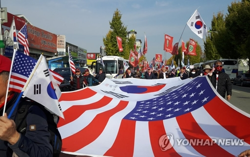 Pro-Trump supporters march on a road near Camp Humphreys in Pyeongtaek, 70 kilometers south of Seoul on Nov. 7, 2017. It was the first stop in the U.S. President Donald Trump's two-day state visit to South Korea. (Yonhap)