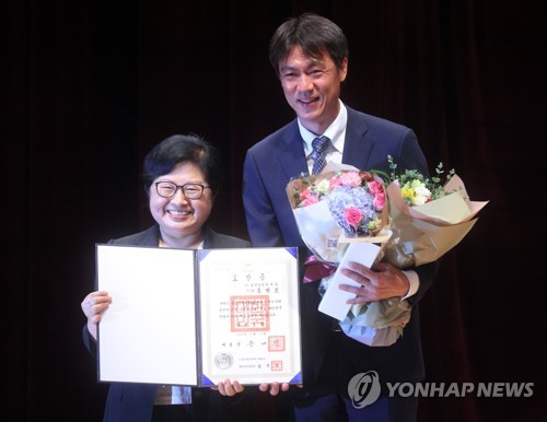 In this file photo taken on July 13, 2017, former South Korea national football team head coach Hong Myung-bo (R) poses for a photo with gender equality minister Jung Hyun-baek after receiving an accolade for his work for youths at an event in Seoul. (Yonhap)