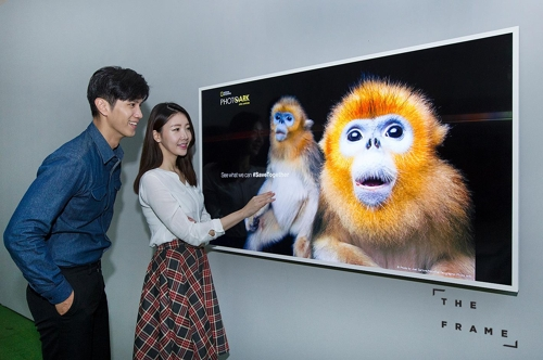 Models pose with Samsung Electronics Co.'s high-end The Frame television displaying a photo of an endangered animal in this photo released by the company on Nov. 9, 2017. (Yonhap)