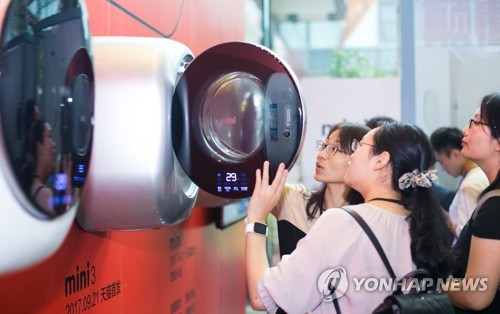 People examine a mini washing machine in this photo provided by Dongbu Daewoo Electronics. (Yonhap)