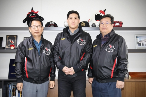 In this photo provided by the KT Wiz baseball club, former major league third baseman Hwang Jae-gyun (C) stands next to Wiz president Yoo Tae-yeol (L) and general manager Lim Jong-taek after signing a four-year deal worth 8.8 billion won (US$7.9 million) with the Korea Baseball Organization team at KT Wiz Park in Suwon, Gyeonggi Province. (Yonhap)