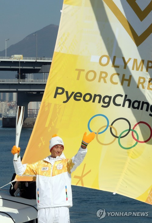 Ha Ji-min, Asian Games gold medalist in sailing, carries the Olympic flame for the 2018 PyeongChang Games as part of the torch relay in Busan on Nov. 6, 2017. (Yonhap)