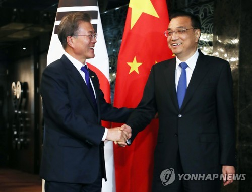 South Korean President Moon Jae-in (L) and Chinese Prime Minister Li Keqiang shake hands before the start of their bilateral talks, held on the sidelines of the Association of Southeast Asian Nations forum in Manila, the Philippines on Nov. 13, 2017. (Yonhap)
