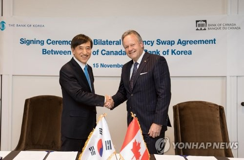 Bank of Korea Governor Lee Ju-yeol (L) shakes hands with his Canadian counterpart Stephen S. Poloz after signing the agreement establishing the swap arrangement at a ceremony at the Bank of Canada's head office in Ottawa, Canada. on Nov. 15. (Yonhap) This photo was provided by the Bank of Canada.