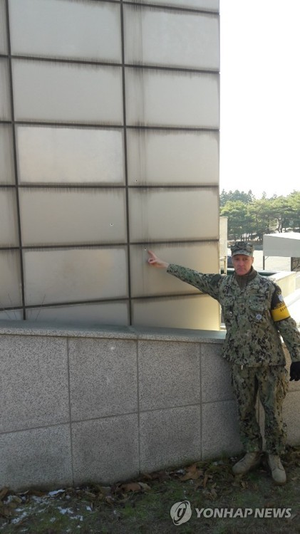 A U.S. military officer shows a bullet trace on the wall of a JSA building resulting from North Korean troops' firing at a fellow soldier defecting to South Korea via Panmunjom in this photo taken Nov. 27, 2017. (Joint Press Corps-Yonhap)