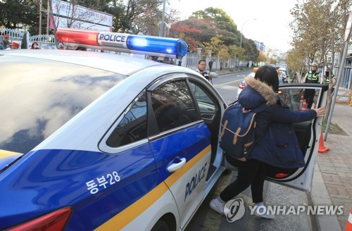 A student gets out of the police vehicle that took her to the test site in the country's southern island of Jeju on Nov. 23, 2017, when the CSAT was held. (Yonhap)