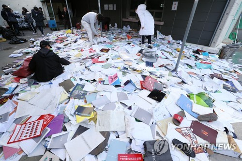 Test-takers search for their books on the rooftop of a private tuition building in central Seoul on Nov. 16, 2017, after the college entrance exam was unexpectedly put off for a week due to the Pohang earthquake that hit the country's southeast a day earlier. (Yonhap)
