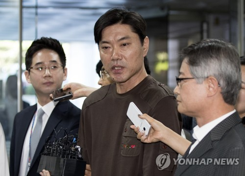 In this file photo taken on Sept. 1, 2017, Choi Kyu-soon (C), a former baseball umpire accused of taking money from professional clubs, speaks to reporters before attending a hearing on his arrest warrant at Seoul Central District Court. (Yonhap)