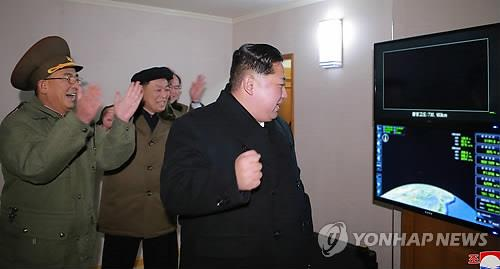 North Korean leader Kim Jong-un pumps his fist while he watches the flight data of the Hwasong-15 missile in this