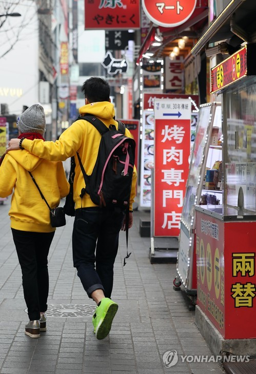 Foreign tourists walk past shops bearing Chinese signs in Seoul's Myeongdong shopping area, one of the top tourist spots in the South Korean capital, on Nov. 28, 2017. (Yonhap)