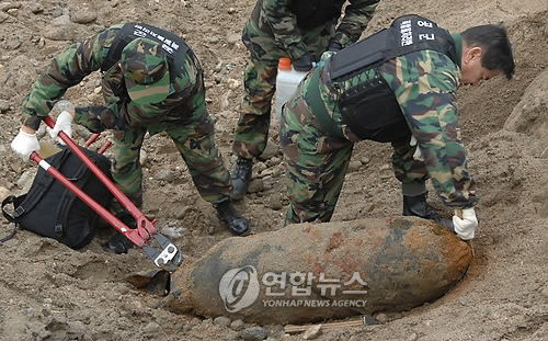 South Korean Air Force soldiers remove an unexploded shell at a construction site in Hoengseong, east of Seoul, in this file photo dated Nov. 28, 2008. (Yonhap)