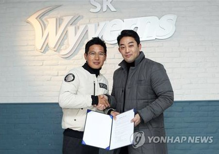 This photo provided by the SK Wyverns on Dec. 7, 2017, shows baseball player Jung Eui-yoon (R) shaking hands with the club's general manager, Yeom Kyung-yup, after signing a new contract. (Yonhap)
