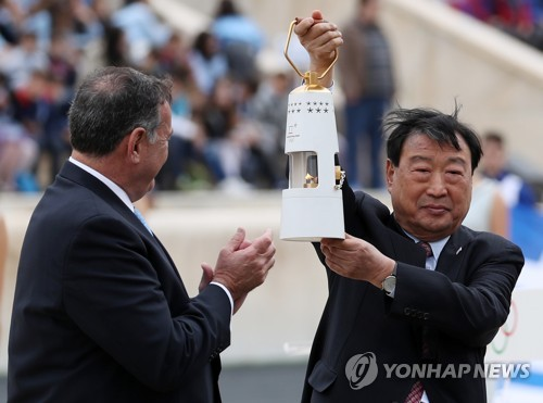 In this file photo taken Oct. 31, 2017, Lee Hee-beom (R), head of the 2018 PyeongChang Winter Olympics organizing committee, holds up a lamp containing the Olympic flame during a ceremony at the Panathenaic Stadium in Athens. (Yonhap)
