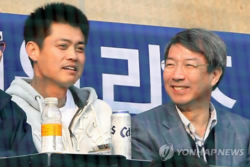 In this file photo taken on April 3, 2011, Chung Un-chan (R), former prime minister named the new commissioner of the Korea Baseball Organization (KBO), attends a KBO regular season game between the Doosan Bears and the LG Twins at Jamsil Stadium in Seoul alongside player-turned-analyst Ahn Kyung-hyun. (Yonhap)