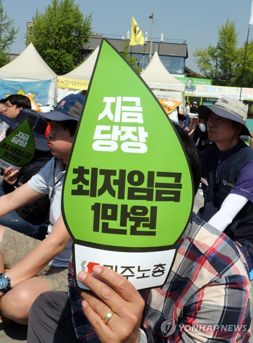 A member from the Korean Confederation of Trade Unions, the smaller of two major labor umbrella groups in South Korea, holds up a banner calling for an increase in the minimum wage to 10,000 won (US$8.68) per hour, as he takes part in a rally in the southwestern city of Jeonju on May 1, 2017, to mark the Labor Day holiday that fell on the same day. (Yonhap)