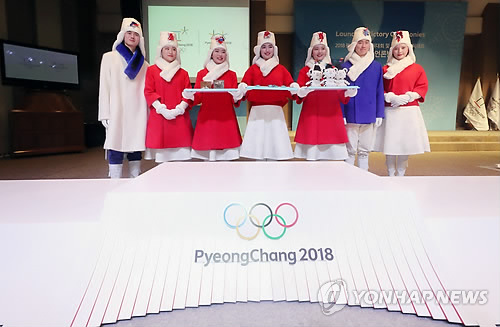 South Korean models wearing costumes for the victory ceremonies at the PyeongChang Winter Olympic and Paralympic Games pose for a photo behind the Olympic podium at an event in Seoul on Dec. 27, 2017. (Yonhap)