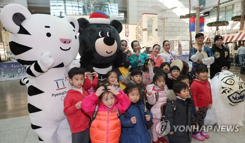 This file photo taken on Dec. 6, 2017, shows South Korean children taking a photo with the PyeongChang Winter Olympic and Paralympic Games mascots at Incheon International Airport. (Yonhap)