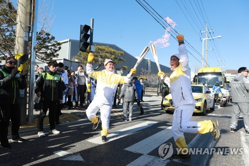 This photo provided by Gumi City Government on Dec. 27, 2017, shows two runners in the Olympic torch relay for the 2018 PyeongChang Winter Olympics in Gumi, North Gyeongsang Province. (Yonhap)