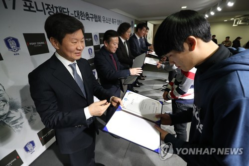 Korea Football Association (KFA) President Chung Mong-gyu (L) hands a certificate of scholarship to a young football player during an event organized by the KFA and the Pony Chung Foundation in Seoul on Dec. 27, 2017. (Yonhap)