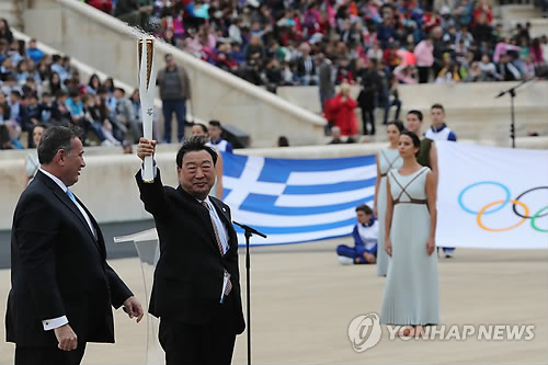 In this file photo taken on Oct. 31, 2017, Lee Hee-beom (2nd from L), the president of the PyeongChang 2018 Organizing Committee, holds the Olympic torch at the Panathenaic Stadium in Athens. (Yonhap)