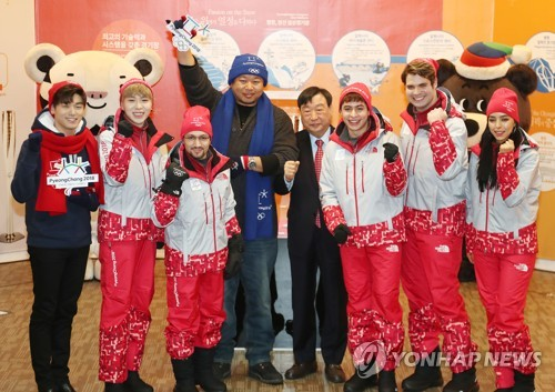 In this file photo taken Dec. 24, 2017, Lee Hee-beom (4th from R), the president of the PyeongChang 2018 Organizing Committee, poses for a photo with honorary ambassadors for the PyeongChang Games and entertainers during a media event in Seoul. (Yonhap)