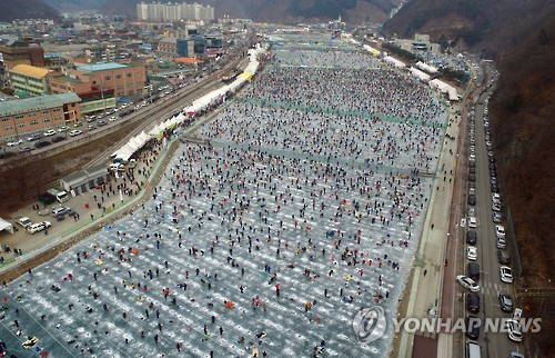 "This 2017 file photo shows visitors crowding onto a frozen river to fish for ""sancheoneo,"" a type of mountain trout, during the annual Hwacheon Sancheoneo Ice Festival in Hwacheon, 120 kilometers northeast of Seoul. (Yonhap)"