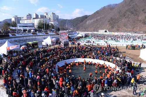 "This 2017 file photo shows visitors catching ""sancheoneo,"" a type of mountain trout, with their bare hands during the annual Hwacheon Sancheoneo Ice Festival in Hwacheon, 120 kilometers northeast of Seoul. (Yonhap)"