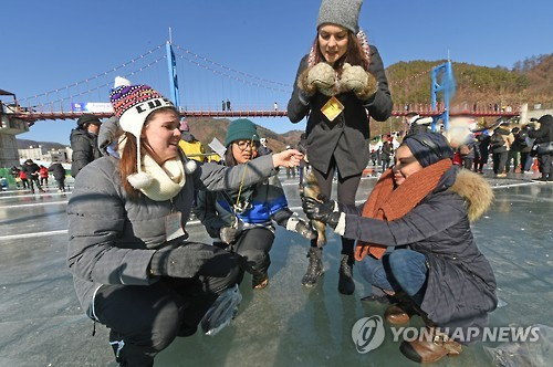 "This 2017 file photo shows foreign visitors fishing for ""sancheoneo,"" a type of mountain trout, during the annual Hwacheon Sancheoneo Ice Festival in Hwacheon, 120 kilometers northeast of Seoul. (Yonhap)"