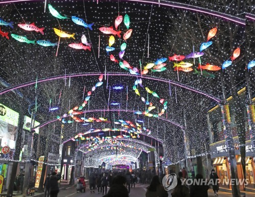 "This 2017 file photo shows visitors walking along a street decked with lamps in the shape of ""sancheoneo,"" a type of mountain trout, during the annual Hwacheon Sancheoneo Ice Festival in Hwacheon, 120 kilometers northeast of Seoul. (Yonhap)"