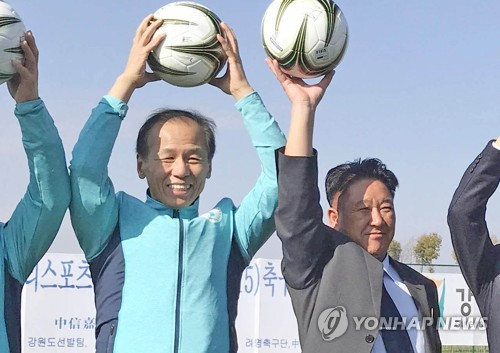 This photo provided by Gangwon Province shows Gangwon Governor Choi Moon-soon (L) posing for a photo with Mun Ung, the chairman of North Korea's April 25 Athletic Committee, at the Ari Sports Cup youth football tournament in Kunming, China, on Dec. 19, 2017. (Yonhap)