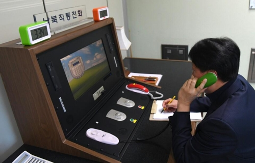 This photo, provided by South Korea's unification ministry, on Jan. 3, 2018, shows a South Korean liaison official contacting his North Korean counterpart via the restored cross-border communication channel. (Yonhap)