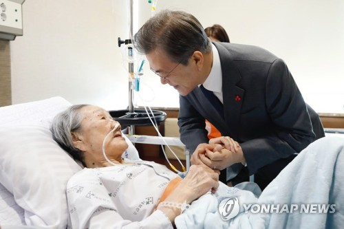 President Moon Jae-in (R) holds a hand of a former South Korean sex slave, Kim Bok-dong, while visiting the 90-year-old at a local hospital in Seoul on Jan. 4, 2018, shortly before his meeting with eight other former sex slaves at his office Cheong Wa Dae. (Yonhap)
