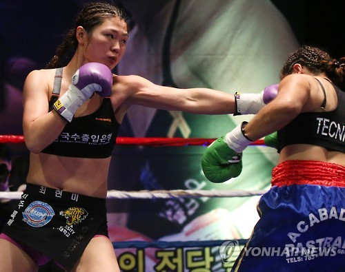 In this file photo taken March 27, 2016, South Korean boxer Choi Hyun-mi (L) delivers a blow to Colombia's Diana Ayala in their World Boxing Association (WBA) women's super featherweight title bout in Gwangmyeong, Gyeonggi Province. (Yonhap)