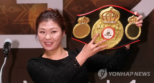 In this file photo taken on Dec. 16, 2013, South Korean boxer Choi Hyun-mi holds her World Boxing Association (WBA) women's super featherweight championship belt at an event in Seoul. (Yonhap)