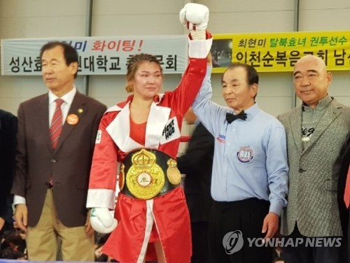 In this file photo taken Nov. 18, 2017, South Korean boxer Choi Hyun-mi (2nd from L) is declared the winner after her World Boxing Association (WBA) women's super featherweight title defense bout in Incheon. (Yonhap)
