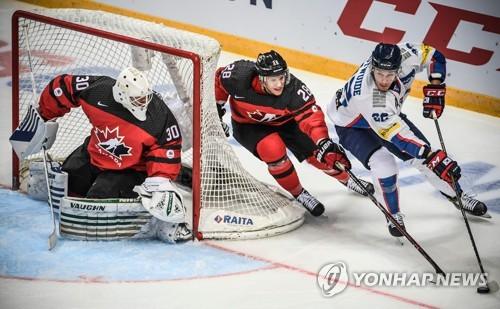 In this AFP file photo taken Dec. 13, 2017, South Korean forward Mike Testwuide (R) controls the puck against Canadian defenseman Mat Robinson (C) during their Channel Cup hockey game at VTB Ice Palace in Moscow. (Yonhap)