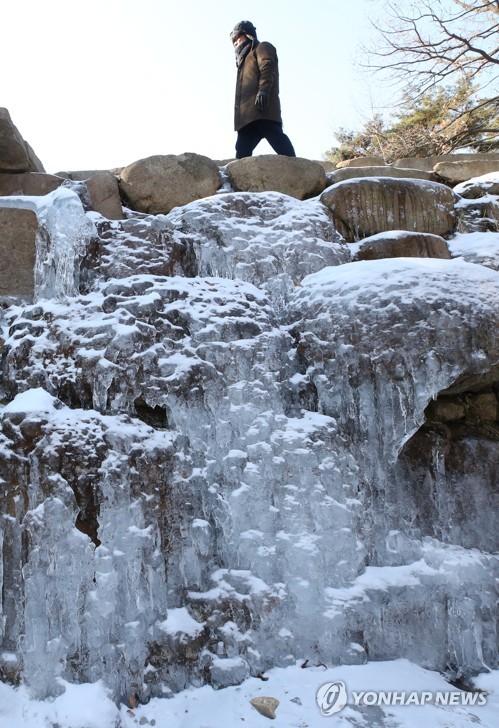 A citizen walks by a frozen waterfall along a trail in Gwacheon, south of Seoul, on Jan. 12, 2018. (Yonhap)