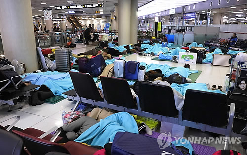 Tourists sleep in the lobby of Jeju International Airport on the southern resort island of Jeju on Jan. 12, 2018, as heavy snow and strong winds caused hundreds of flight cancellations and delays the previous day. (Yonhap)